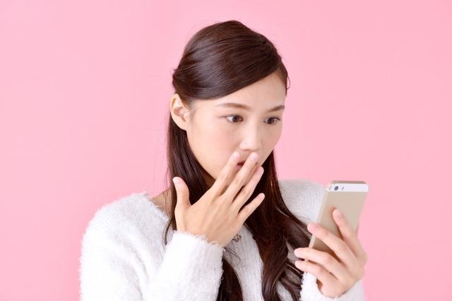 スマホとにらめっこする女性のイメージ画像